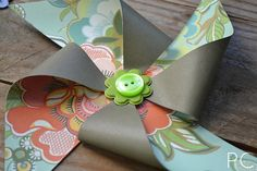Pinwheels made out of scrapbooking paper and buttons.... Add # to center for table numbers