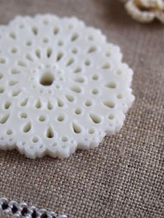 This is a soap which has fine lacework on it.    I siliced a soap about 7-8 mm thick, and cut out flower shape with a cookie cutter. And I pierced small holes by using needles, toothpicks and a straw.    At first I thought it was easy to make, but it took 2 hours to make 1 doily. When made a hole, the edge of the hole upheaved. It took a long time to cut the upheaval off.