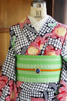 白に黒のラインで縁取られた四角い水玉が格子のようにならなんだモダンデザインをベースに、優しい緑と深い赤にふわりと淡い黄色がぼかされた色合いも美しく、大輪の菊花模様が染め出された注染レトロ浴衣です。