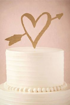 A gold heart and arrow cake topper goes well for a wedding at any time of year, especially a Valentine's Day wedding.