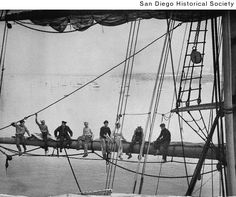 "Group of men sitting on the mainsail yard of the ""Star of India"". San Diego"