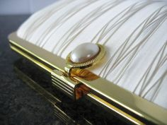 Beautiful pleated clutch handbag in a beautiful creamy white. Featured a oval pearl clasp and goldtone structure and long chain  Brand new/never used