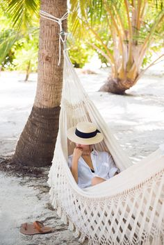 Knotted White Button Down Shirt with Cuffed Sleeves, Wide Brimmed Straw Hat with Black Ribbon, Cream Lace Hammock Among the Palm Trees // take a tropical getaway & relax