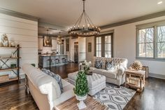 Farmhouse design, vintage decor, Fixer Upper style, farmhouse elements, shiplap walls, patterned rug, tufted ottoman, neutral color palette