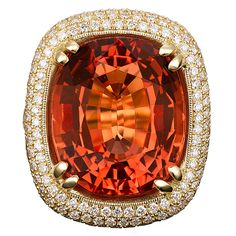 estate ring with an impeccable Brazilian Imperial topaz. Weighing an incredible 31.85 carats, a fiery orange hue, complemented by 4.21 carats of pavé-set diamonds. Nestled into a custom-made, 18K yellow gold setting, this topaz is truly in a class of its own. Beloved by the czars of Russia, Imperial topazes are among the most fascinating gemstones in the world. Found only in Ouro Prêto, Brazil. German Foundation for Gemstone Research as a Natural and unmodified Brazilian topaz.