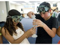 Fifth grade students Tatyana Gonzalez and Nica Rahmati, from left, start an experiment using dry ice with acids and bases at De Portola Elementary School in Mission Viejo on Monday. Farokhi Inspires Youth in Science teaches kids science concepts through hands-on experiments.