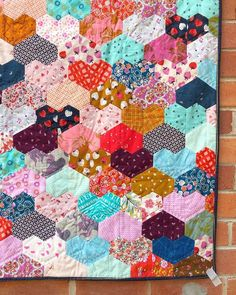 """I'm so glad to have my heart quilt back in my arms! Just in time for Valentines! To celebrate, Jewels of all sizes are 20% off until Wednesday! My #warmheartedquilt pattern can be found in this month's issue of @lovequiltingmag, and was made using 1 1/2"""" jewels. It's the EASIEST EPP I've ever worked on. Perfect for beginners! #cottonandsteel #lovepatchwork"""