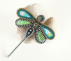 A dragonfly brooch handcrafted using recycled zippers and Japanese chiyogami paper.
