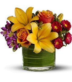 Tropical centerpiece created using Asiatic lillies, orange roses, purple alstroemeria and red Matsumoto asters.