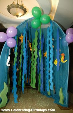 Mermaid Birthday Party Entrance -A canopy filled with streamers all in blue, green and purple served as an entrance. Guests walked in through the streamers and entered the party area.