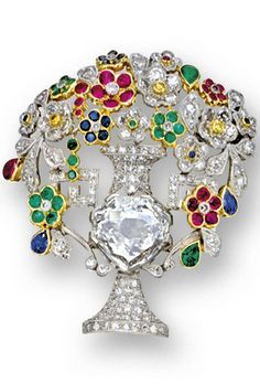 DIAMOND AND GEM-SET BROOCH The vase centring on a shield-shaped diamond weighing approximately 3.10 carats, the bouquet of flowers set with pear-shaped and circular-cut rubies, sapphires, emeralds and diamonds, the diamonds together weighing approximately 1.85 carats, mounted in platinum, retractable pendant fittings.