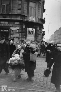 Jewish pedestrians crossing at the intersection of Chlodna and Zelazna Streets in the Warsaw ghetto, doff their hats to the German photographer