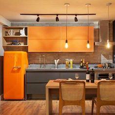 Não há nada mais masculino que assumir o estilo industrial na hora de decorar. Neste espaço as linhas retas e iluminação em trilhos ganham calor ao serem confrontados com os móveis e os revestimentos de madeira. Para deixar o estúdio com a cara de um jovem solteiro, a combinação moderninha de cinza e laranja foi a escolha quanto à paleta de cores. #arquiteto #decor #arquitetura #designdeinteriores #luxo #instadesign #pantone #kitchen #wood #design #arquitetura #inspiração