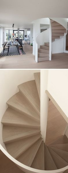 This light wood spiral staircase twirls up around a central shaft, while the white handrail helps the stairs blend in with the surrounding interior.