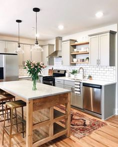 Love this farmhouse style kitchen, wood island, gray cabinets, open shelving