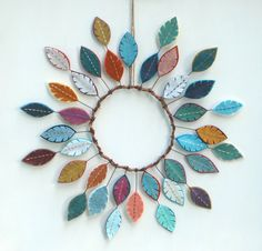 This beautiful, unique design will set your decor apart from the rest. Dozens of hand-embroidered felt feathers radiate from a circle of
