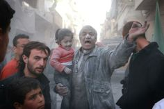 A Syrian man holds a crying girl as he gestures following an air strike by government forces on the Sahour neighborhood of the northern Syrian city of Aleppo on March 6, 2014.