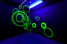 """Paolo Scheggi, Interfiore, 1968, pittura gialla fluorescente su anelli di legno e luce di Wood, dimensioni variabili e ambientali, """"Paolo Sc..."""