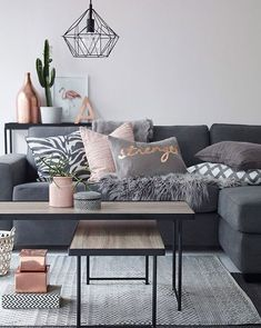 Beautiful living room with dark grey sofa, different throw pillows and extraordinary pendant lights