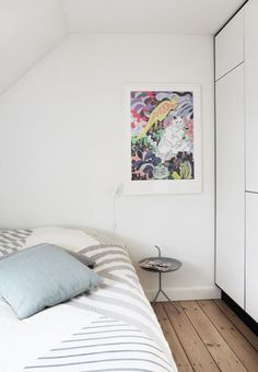 Soft toned bedroom with side table from the Danish brand, HAY. The colours are kept in a white/grey theme.