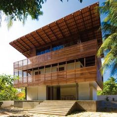 Casa Tropical: Project: Casa Tropical Architect: Camarim Architects Project Location: Ceara, Brazil Project Date: 2013Located in a fishing village with both wet and dry season, this holiday house invites the outside as much as possible. This also helps with natural sustainability options such as where the suspended roof  and the wooden facade both protect the house from the sun while being permeable,  the cool southern wind cross ventilates so that there isn't a need for air conditioning.: