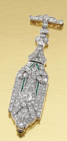EMERALD AND DIAMOND LAPEL WATCH, 1920S.  The rectangular dial applied with Arabic numerals, encased within a cartouche-shaped frame decorated with ribbon motifs and millegrain-set throughout with circular-, single-cut, pear- and triangular-shaped diamonds, further embellished with calibré-cut emeralds, to a diamond-set surmount.