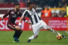 Torino's defender Leandro Castan from Brazil (L) fights for the ball with Juventus' forward Mario Mandzukic from Croatia during the Italian Serie A football match between Torino and Juventus at the Grande Torino Stadium in Turin on December 11, 2016. / AFP / MARCO BERTORELLO