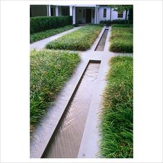 Contemporary water rill with grasses, paths and house in background - The Odrich Garden, Greenwich, Connecticut, USA