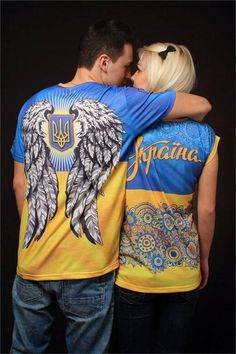 There is more than meets the eye in this photo capture of this couple wearing nationalistic T-shirts. The man can be depicted as soldier or defender of Ukraine (The wings are also an emblematic of the Euromaidan and all soldiers who sacrificed for Ukraine) - AND - the woman wearing the word 'Ukraine' all the more can be seen as the country/nationhood of Ukraine itself ...as if Ukraine was a lady to be loved & cherished, kept close to heart, respected, protected & defended from harm. VERY…