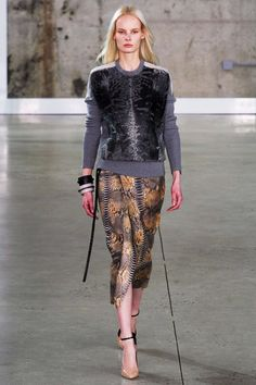 Reed Krakoff, New York Fashion Week Fall 2014. Pullover with fur-like front print, grey sleeves and rib, wrap skirt in a snake patterned flared fabric, nude heels with black straps, chunky bracelets.