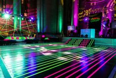 Inspired by an image of laser lighting, Evoke's design team used neon green and pink tape to turn the dance floor into the event's laser-esque focal point. Photo: MBK Photography