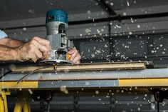A man using a woodworking router to trim a laminate table top by Adam Nixon