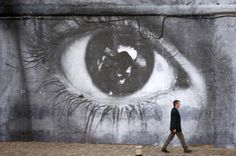 """Paris, France While Paris has a lively street art culture, native JR has garnered the most international fame. JR has exhibited his giant black-and-white photos in cities all over the world from Japan to Palestine to New York. In 2009, JR decorated the River Seine with this image of a woman's eye for part of his """"Women Are Heroes"""" exhibit where he covered public spaces across the globe with images of women."""