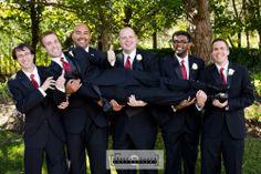 Groomsmen picking up groom, fun with groom, groom swept off his feet, thumbs up from groom, red tie, white flowers.