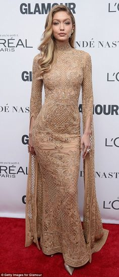 Going for gold: Meanwhile catwalk queen Gigi displayed her show-stopping figure in a slinky nude lace gown, embellished with delicate gold sequins all over