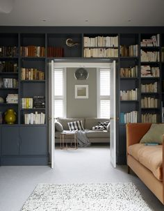 Library-style book shelves that frame a door allow you to make the most of every inch of storage space. Be restrained with what you display - keep to neutral colours and a limited number of different objects. Image: Livingetc