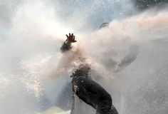 A protester tries to remain standing as police use a water cannon during clashes at Taksim Square in Istanbul, Turkey, on June 11, 2013. Hundreds of police in riot gear forced their way through barricades in the square early Tuesday, pushing many of the protesters who had occupied the square for more than a week into a nearby park.