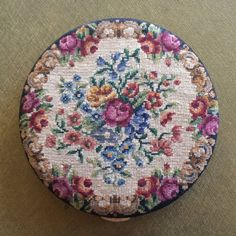 """Very pretty mirrored powder compact. Genuine handmade petitpoint by Schildkraut 1650 stitches to the square inch. Floral design petitpoint on the top and black fabric covered back. Original Schildkraut foil label is intact on the framed mirror. Powder sifter and puff in place. This compact is also marked, """"Lin-Bren Patent 2425540"""". This patent was applied for in 1946. This is a fairly large compact with a diameter of about 3 3/8"""". This compact measures approximately ½"""" thick.  The handmade…"""