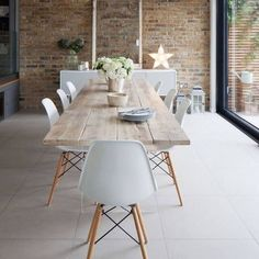 White and brick dining room featuring eiffel chair #diningroomfurniture