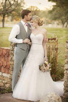 This modified designer A-line wedding gown from Essense of Australia adds the right amount of romance to your wedding day. The fitted, strapless bodice is made from elegant, heirloom-inspired lace. The tulle skirt blooms gracefully into a chapel train. Your choices include clear beading or Diamante embellishments, and a corset closure or an easy-zip back closure under fabric-covered buttons. (sp)