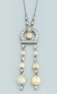 An early 20th century pearl and diamond pendant necklace, by Marcus & Co  The pendant composed of graduated pearl and square-cut diamond flexible line twin drops to a single and baguette-cut diamond horseshoe surmount with pearl centre, baguette and single-cut diamond two stone suspension and trace link neckchain, circa 1905