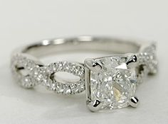 Beautiful and delicate, this diamond engagement ring is designed with two bands of micropavé set diamonds intertwined around one another to frame your center diamond.