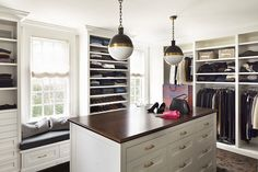 Fabulous, walk-in closet boasts Small Hicks Pendants illuminating wood topped closet island with drawers used to hold jewelry accented with brass pulls across from floor to ceiling, built-ins housing clothes and shoes flanked by built-in window seats.