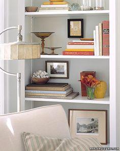 Smaller art/picture frames hung in a bookshelf..