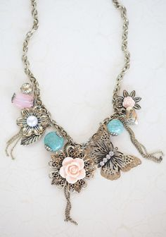 "Floral Oasis Necklace 22.99 at shopruche.com. Reminiscent of vintage treasures found in the attic, this charming brass necklace holds nature-inspired charms polished with glowing faux pearl and sparkling rhinestone accents.17"" long"