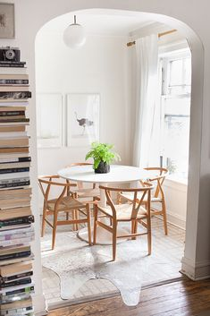 Modern, all-white dining space with cowhide rug, wood chairs, and stacked books