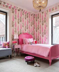 Chic girl's bedroom features pink and brown wallpaper framing pink Baroque bed dressed in white and pink geometric bedding paired with mirrored 1-drawer nightstand situated next to gray tufted storage bench used to store toys placed under window as well as purple and pink suzani foot stool atop cream herringbone rug.