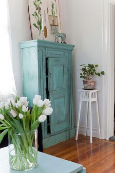 Tulpaner sprider vårkänsla på vardagsrumsbordet. Det blå skåpet stod i gårdens uthus. Mademoisellestolen är köpt på auktion.