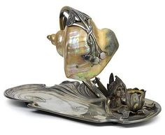 Gustav Gurschner, attribution, Art Nouveau electric table lamp with attached tray and candleholder, wood fairy and seashell shade, manufactured by Moritz Hacker, Vienna, c. 1905, brass with remains of silver plating, impressed factory mark onn the underside, height 23 cm, length 36.5 cm