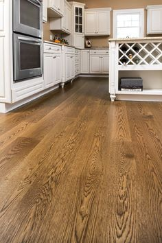 Wide plank white oak, finished with medium brown stain and high resin tung oil. Stunning with white cabinets.